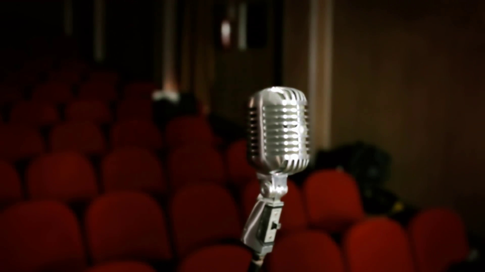 1920x1080 Microphone vintage theater red. A retro vintage shiny microphone on the  stage of a theater or cinema. Red seats in the background.
