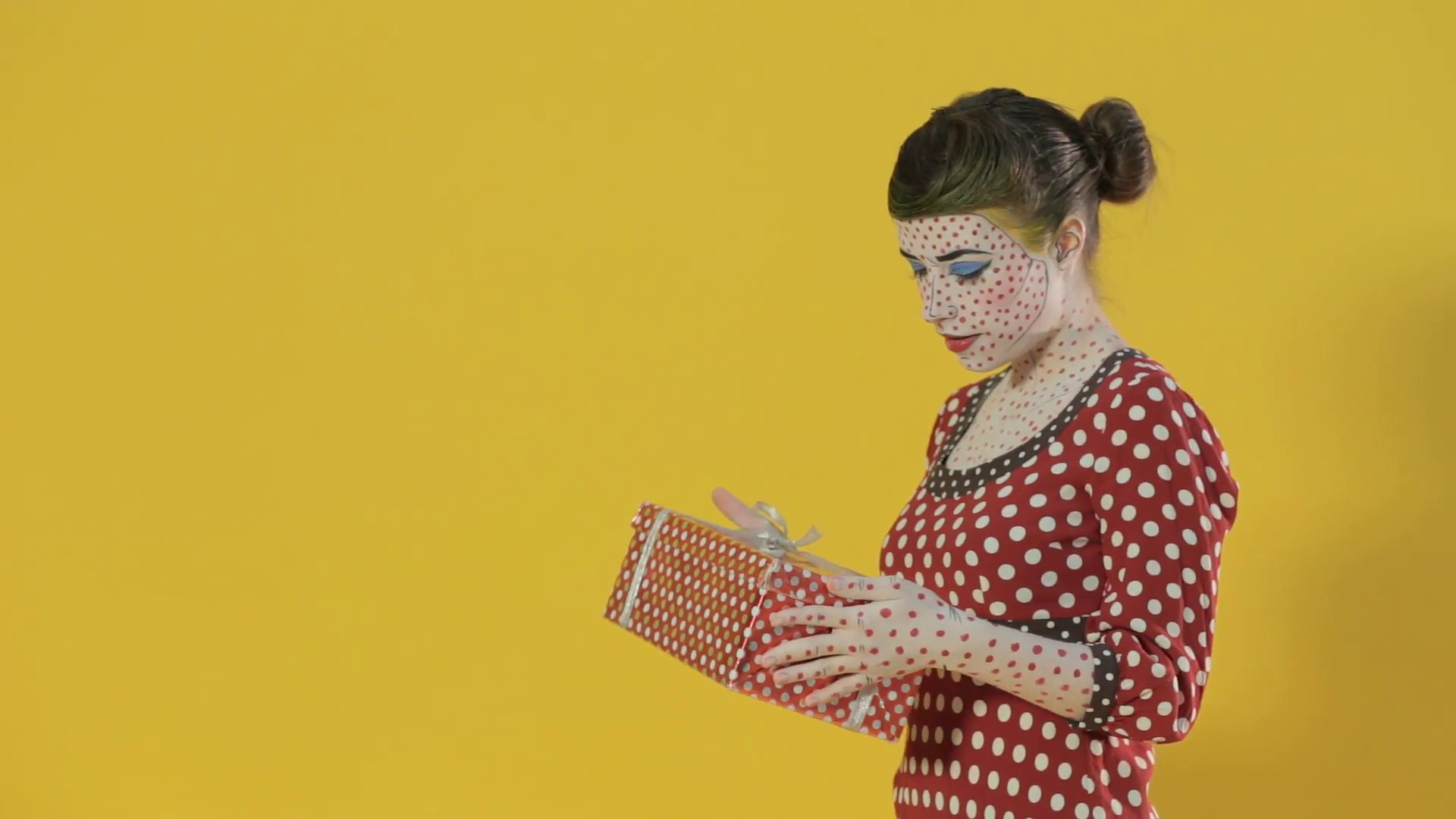 1920x1080 Girl made up as girl from the comics on a bright yellow background with a  gift Stock Video Footage - VideoBlocks