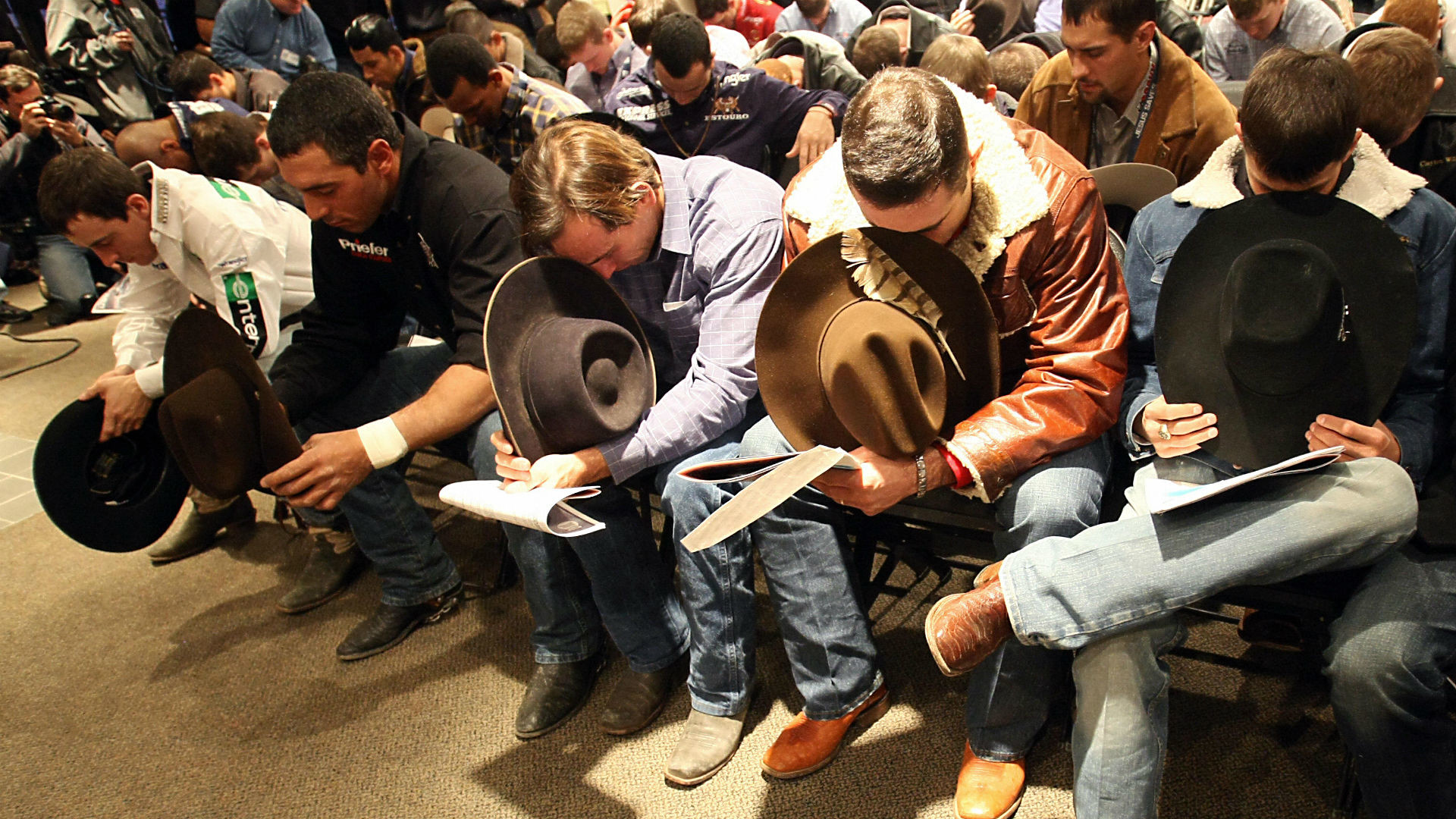 1920x1080 PBR cowboys pray before an event. (Getty)