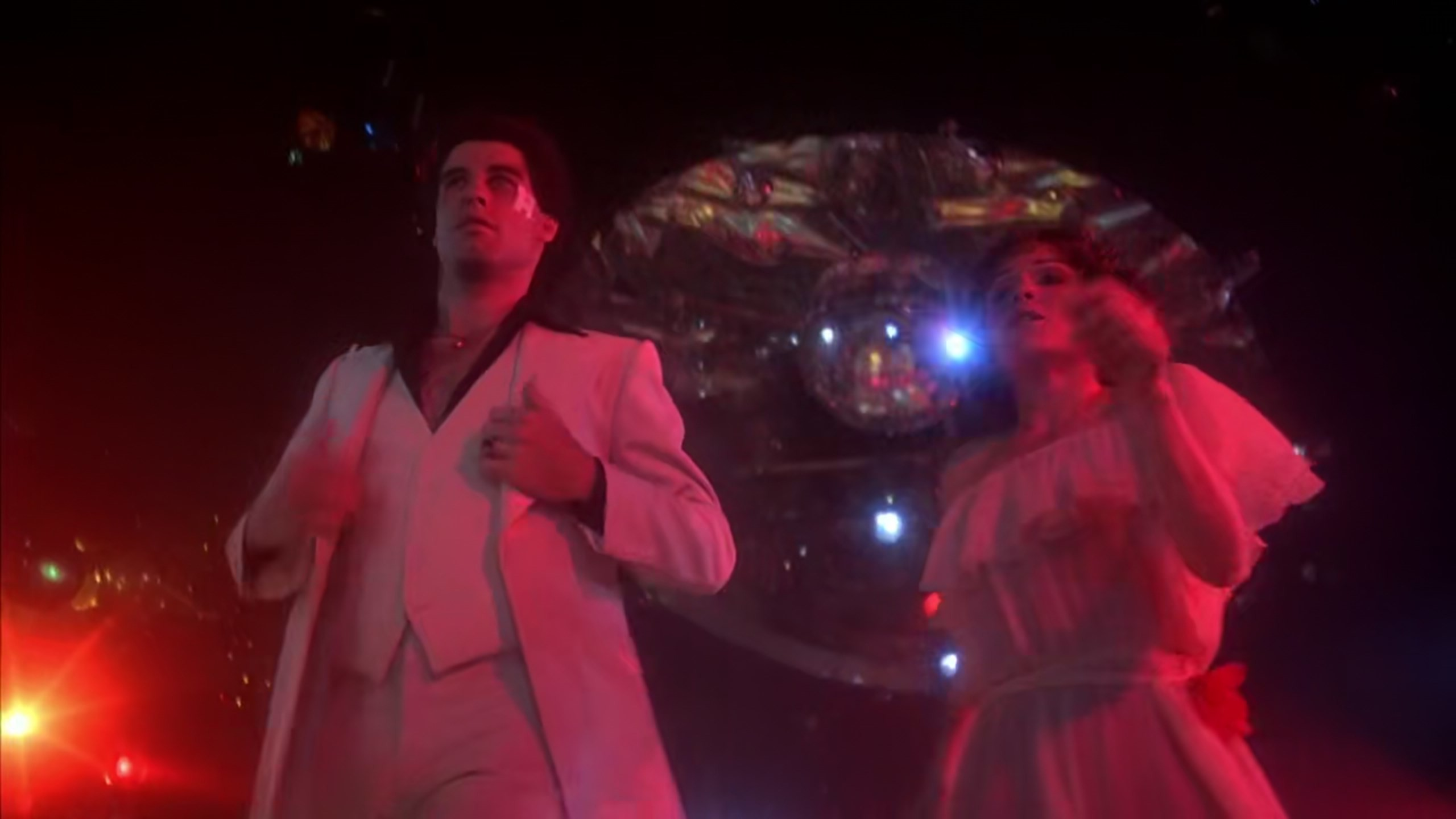 2560x1440 Saturday Night Fever (1977), dir. John Badham. From the first scene Badham  shows the disco lover as a lower class worker. John Travolta, as Tony  Manero, ...